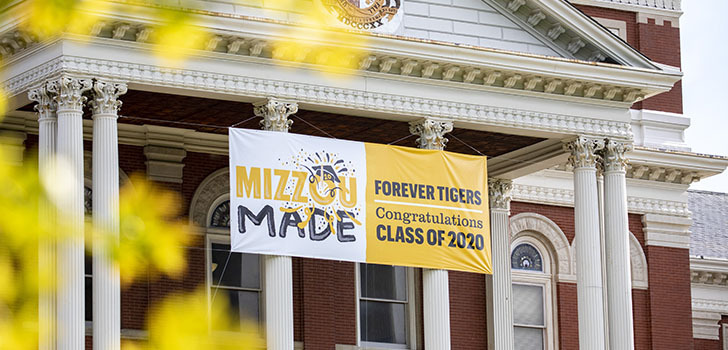 "A view of Jesse Hall through some leaves - there is a sign that says ""MizzouMade Forever Tigers Congratulations Class of 2020"""