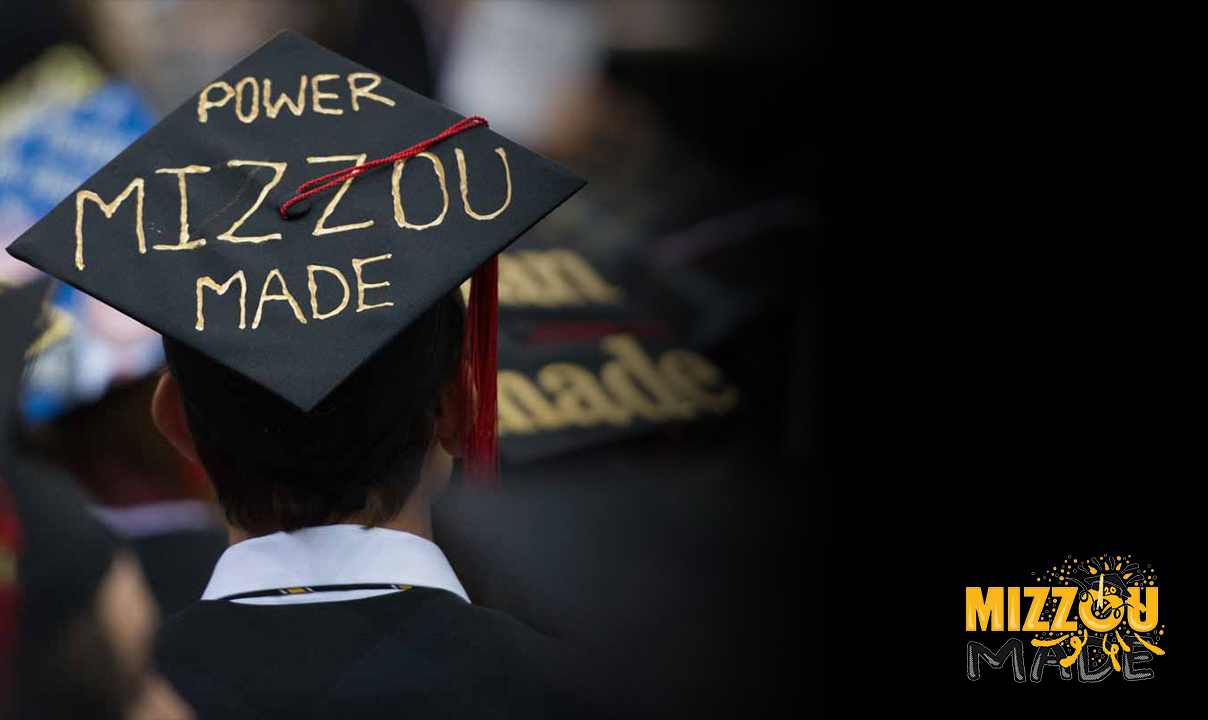 Image of the back of a man's head wearing a black graduation cap decorated with gold lettering