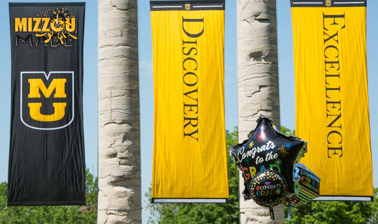 Photo of two stone columns hung with black and gold banners. The three banners are decorated with a gold Stacked
