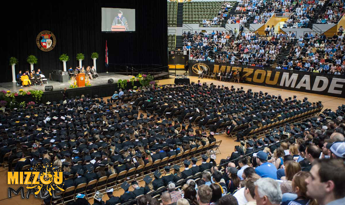 """Photo of students in black graduation robes and caps seated to face a stage with a speaker at a podium. In the corner is a hand drawn gold bubble """"Mizzou"""" and black """"Made"""" stacked underneath it. The 'o' in the Mizzou has a graduation cap with confetti shooting out."""