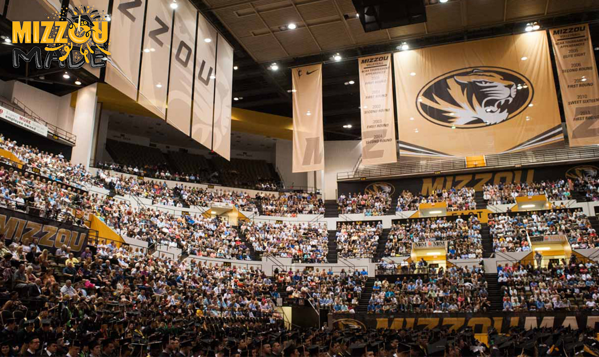 Photo is of a multi-tiered arena filled with graduating students and family members. Banners hang from the rafters spelling out