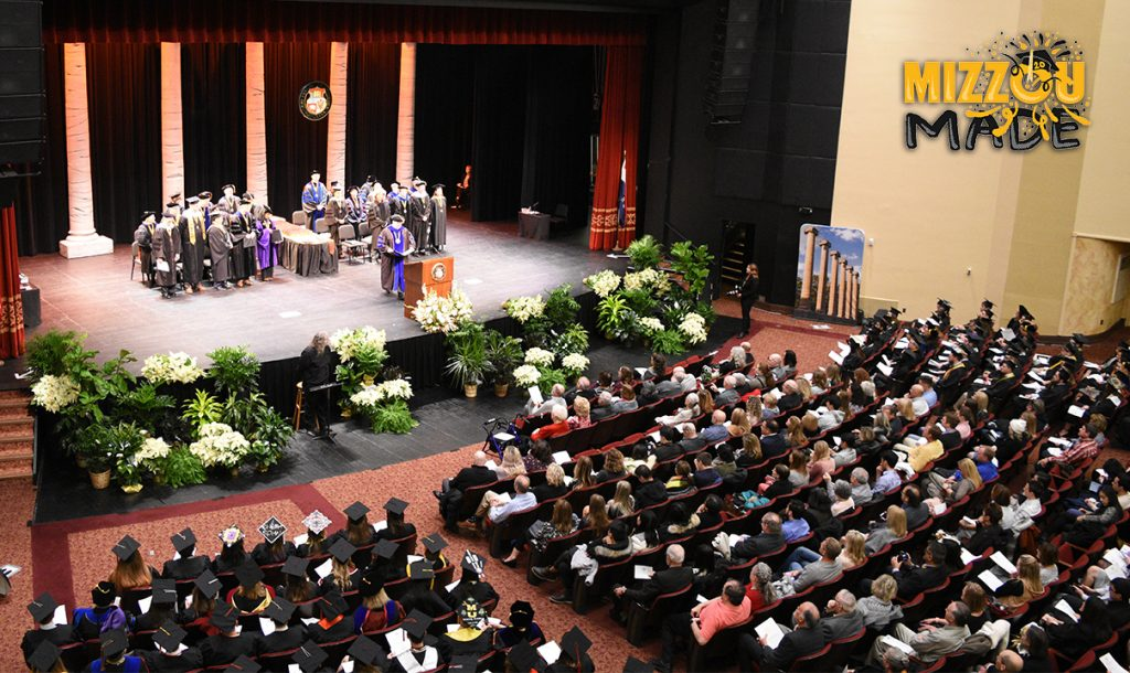 """Students sit in black graduation robes and caps facing a stage. On the stage are professors in black and purple robes standing behind a podium. In the upper right corner is a hand drawn gold bubble """"Mizzou"""" and black """"Made"""" stacked underneath it. The 'o' in the Mizzou has a graduation cap with confetti shooting out."""